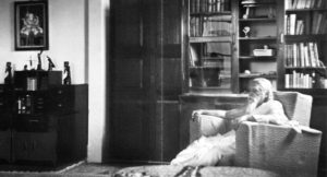 Sri Aurobindo, seated in his chair - in his room
